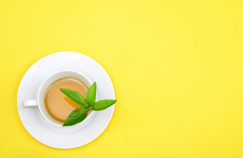 mint tea on yellow background Food Top View Vegetable Yellow Cup Hot Drink Drink Tea Leaf Mint Tea Mint Leaf - Culinary Yellow Yellow Background Colored Background Leaf Studio Shot Healthy Lifestyle Copy Space Close-up Tea Leaves Sour Taste Vegetarian Food Leaf Vegetable Vegan Tea Ceremony