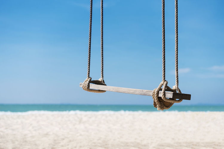 Close-up of swing hanging over sand at beach against sky