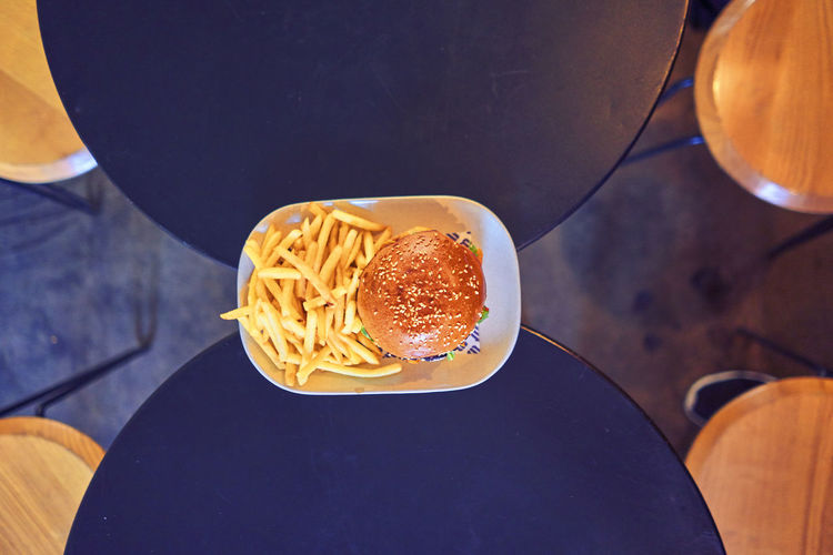 Directly above shot of burger and french fries in plate on tables at restaurant