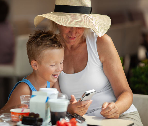 Grandmother and grandson using mobile phone while sitting on table