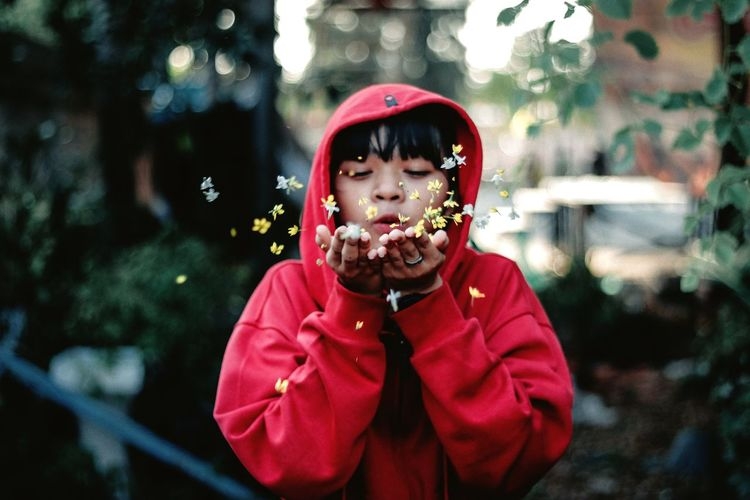 Girl wearing hooded shirt while blowing flowers