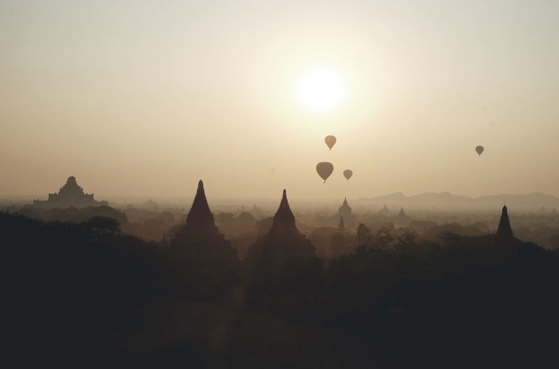 Hot air balloons flying over city during sunrise in foggy weather