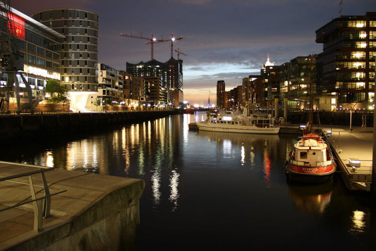 Boat moored in river against illuminated buildings