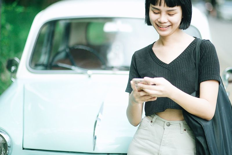 Young woman using phone while standing by car