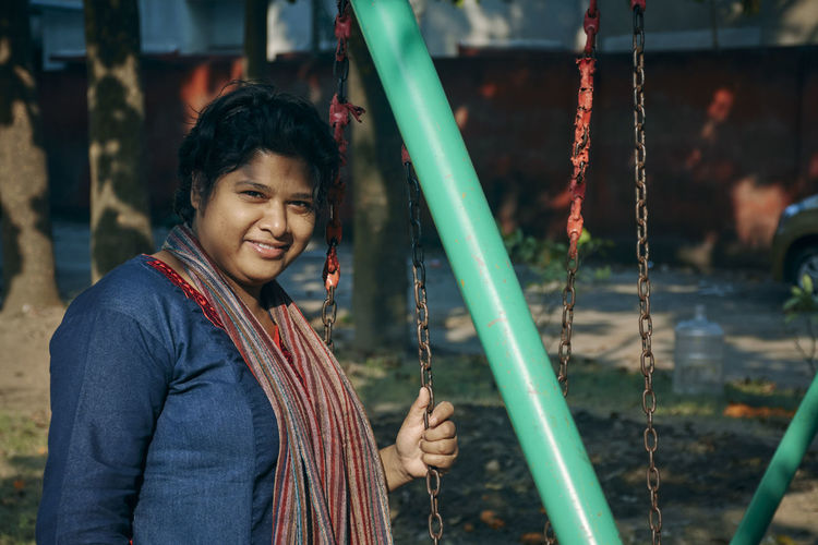 Casual looking fashionable indian woman leisurely spending time in public park, standing near swing