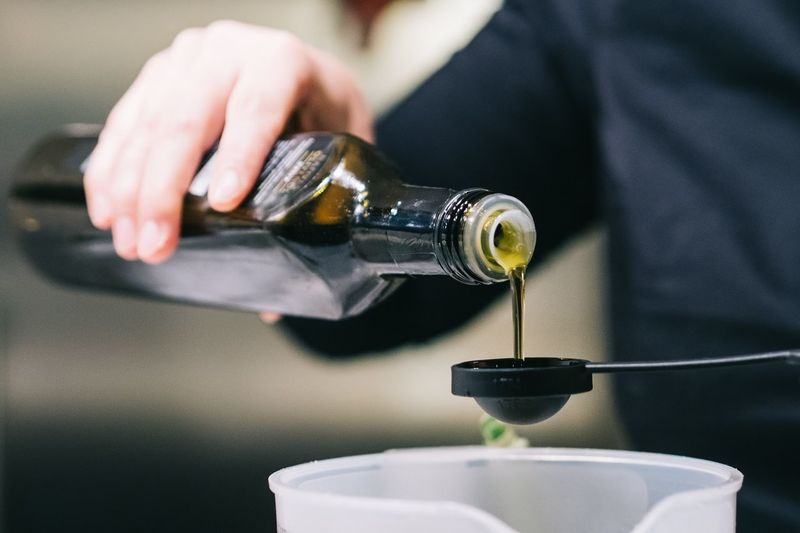 Cropped image of person pouring oil from bottle