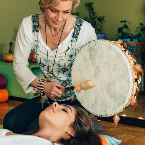 Therapist Playing Drum By Young Woman At Spa