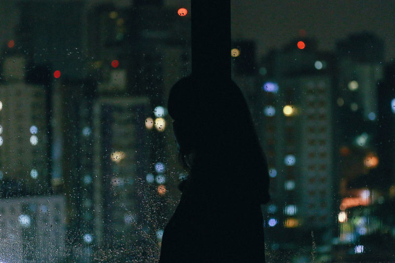 Woman looking through window at night