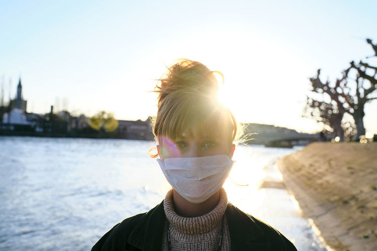 Portrait of woman wearing mask standing against lake