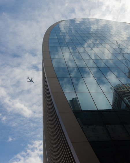 EyeEm Best Shots A New Beginning Air Vehicle Airplane Architecture Building Building Exterior Built Structure City Cloud - Sky Day Flying Glass - Material Low Angle View Mode Of Transportation Modern Nature No People Office Building Exterior Outdoors Reflection Sky Skyscraper Transportation