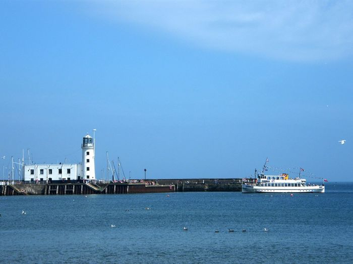 Tranquil seascape with lighthouse and cruise ship
