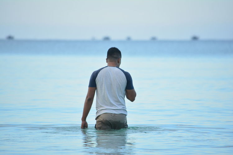 Rear view of man wading in sea against sky
