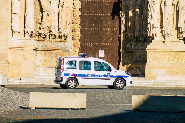 Police car on street against ancient sculptures