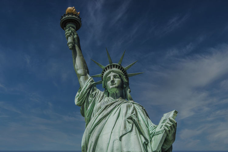 Low angle view of statue of liberty against sky