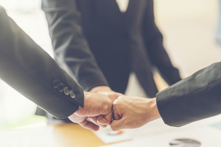 Close-up of business people bumping fist at office