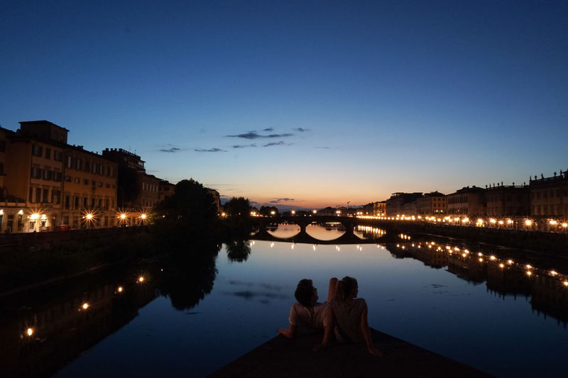 Rear View Of Man And Woman Sitting By River At Dusk