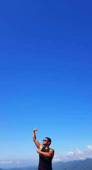 Man gesturing while standing against blue sky