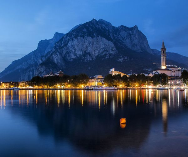 Scenic view of lake with light reflection against mountains