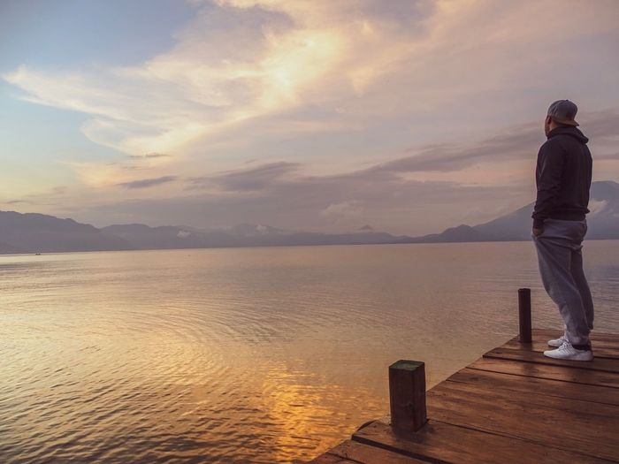 Tranquil scene. Water Sky One Person Sea Beauty In Nature Cloud - Sky Full Length Scenics - Nature Sunset Tranquility Standing Tranquil Scene Rear View Nature Men Land Vacations Outdoors