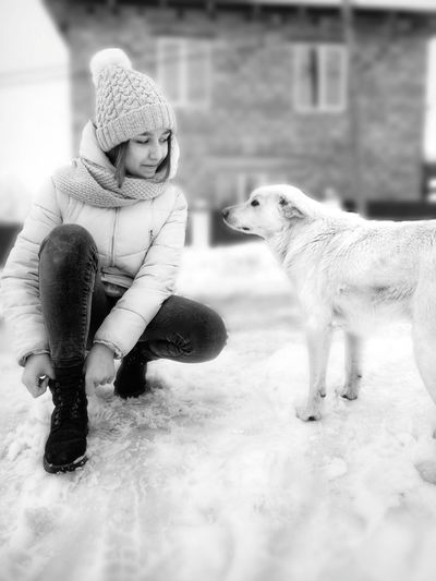 Smiling teenage girl wearing shoe by dog on snow covered road during winter