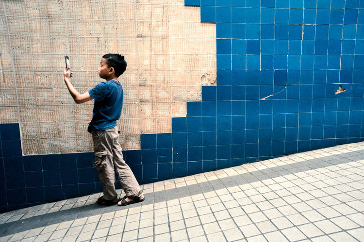 Full length of boy taking selfie through mobile phone while standing on footpath against tile wall