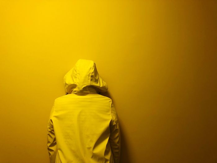 Rear view of person wearing hooded shirt standing against yellow wall