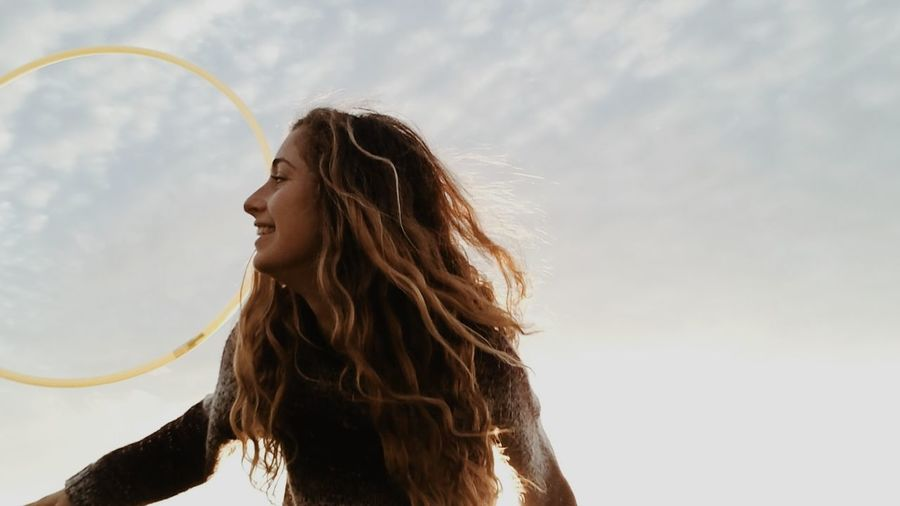 Low angle view of young woman with plastic hoop against sky
