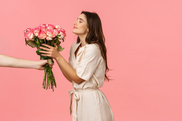 Woman holding rose while standing against pink background