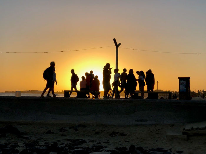 People silhouetted against the setting sun, pier of Santa Maria, Sal Island, Cabo Verde Sunset Sky Group Of People Silhouette Beach Sea