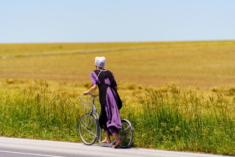 Side view of woman cycling on road