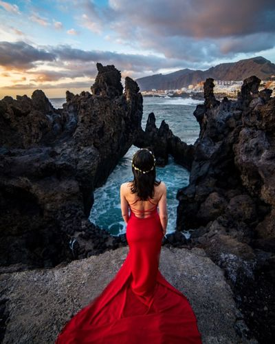 Rear view of woman wearing red dress while standing on cliff