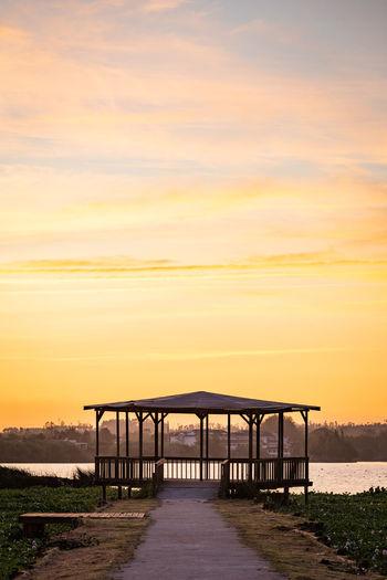 Bridge over sea against orange sky