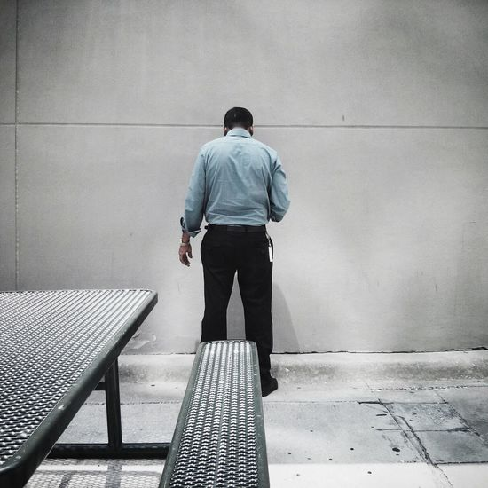 Rear view of businessman against wall with picnic table in foreground
