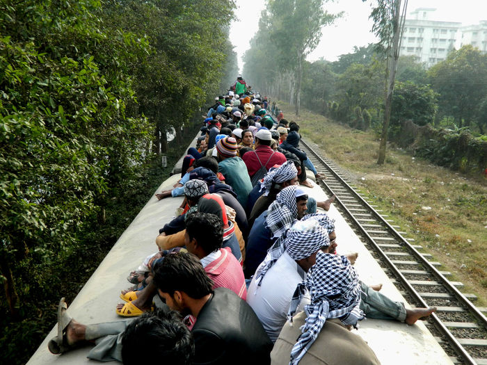 People traveling on rooftop of train