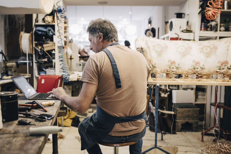 Rear view of male upholstery worker using laptop at workbench in workshop
