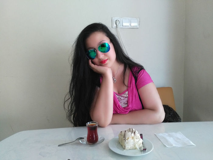 Young woman sitting by dessert and drink at table in cafe