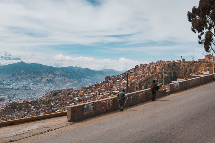 Going up to El Alto. A city that lies 4,150m over sea level. La Paz and El Alto are connected by a cable car made by an Austrian company. The city is also accessible by a steep and dangerous road. A car wreck that hangs inbetween the cliffs should be enough of a sign. El Alto Graffiti Latin America Old Man Panorama Public Transportation Skyline Transportation Built Structure Cityscape Group Of People Looking At View Mountain Mountain Range Outdoors People Real People Residential District Snowcapped Mountain South America Street Travel Destinations Two People Walking Wall The Street Photographer - 2018 EyeEm Awards The Traveler - 2018 EyeEm Awards