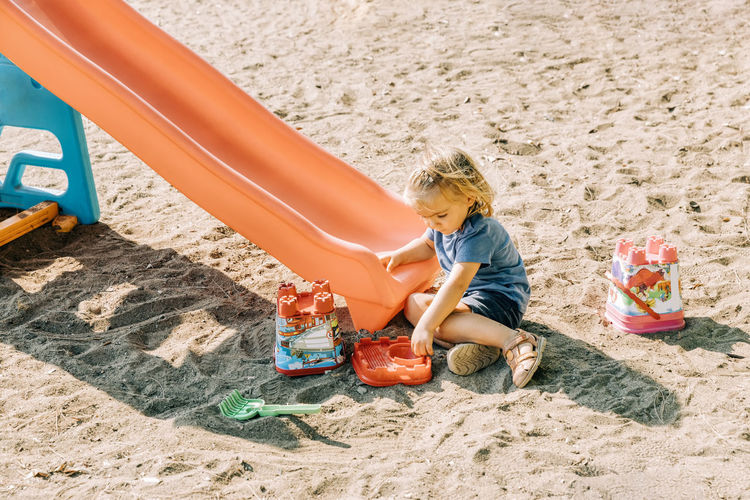 High angle view of boy playing with toy on sand