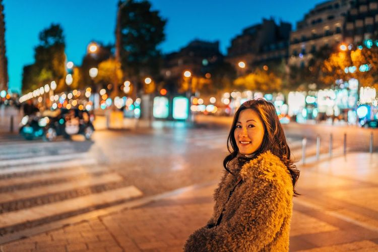 Portrait of smiling woman in illuminated city at night