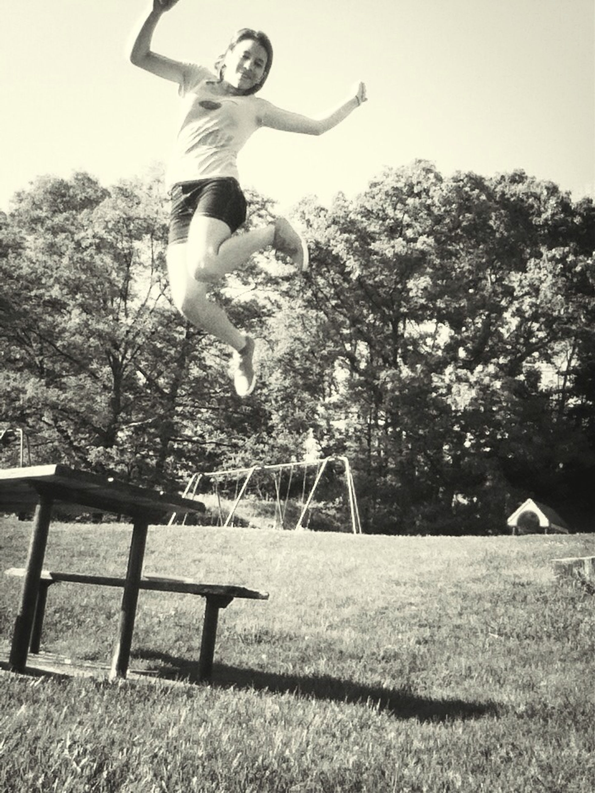 lifestyles, leisure activity, tree, full length, mid-air, childhood, jumping, casual clothing, person, fun, young adult, sport, enjoyment, sunlight, grass, park - man made space, skill, field