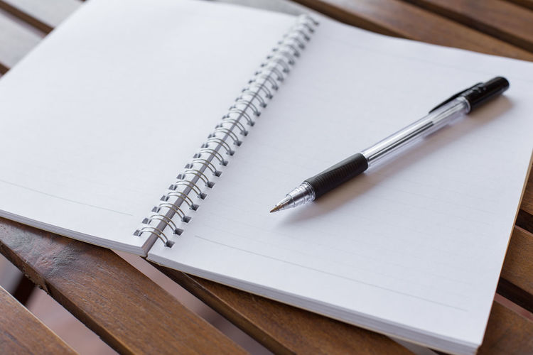 Close-up of pen on open book over table