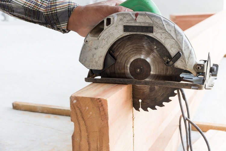 Close-up of man working on wood with circular saw