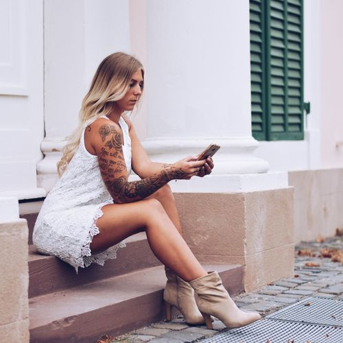 Fashionable woman using phone while sitting on staircase outdoors