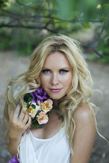 Portrait of blond female with wavy hair and blue eyes, posing in romantic style in the forest. Young beautiful woman wearing white dress and flowers Beautiful Woman Beauty Blond Hair Bouquet Flower Flower Arrangement Flower Head Flowering Plant Front View Hair Hairstyle Leisure Activity Lifestyles Long Hair Looking At Camera Nature One Person Outdoors Plant Portrait Women Young Adult Young Women