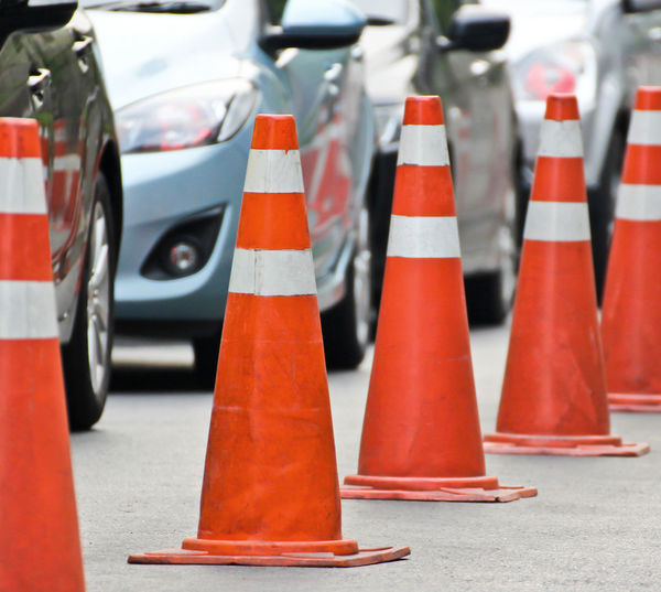 Close-up of red traffic cones on road in city