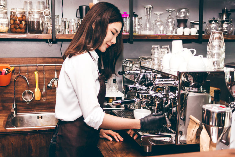 Women Barista using coffee machine for making coffee in the cafe Adult Bar Counter Barista Business Cafe Coffee Maker Coffee Shop Drink Food And Drink Glass Hairstyle Indoors  Lifestyles Long Hair Occupation One Person Preparation  Real People Refreshment Standing Waist Up Women Working Young Adult Young Women