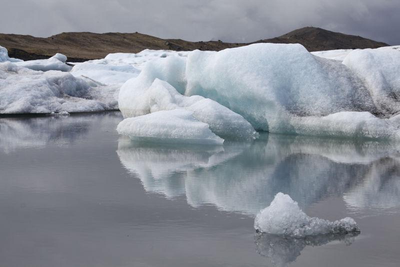 Glaciers On Lake Against Sky