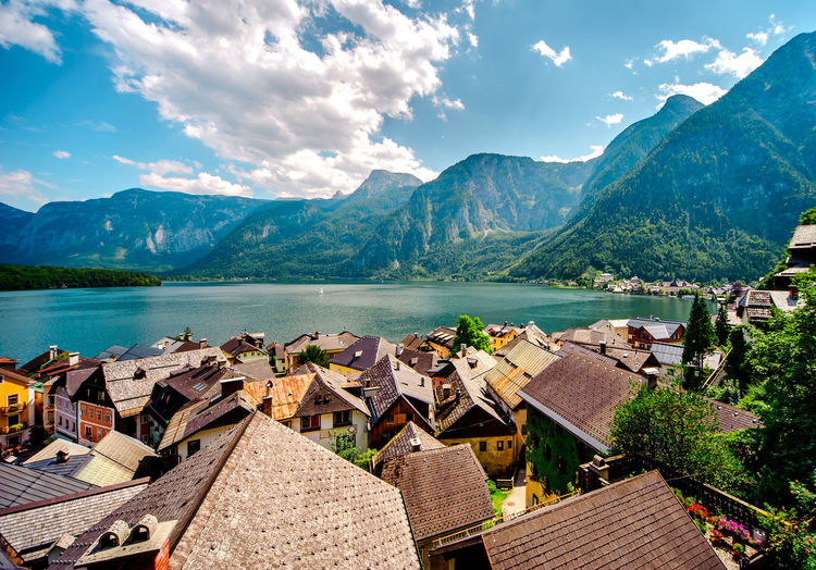 Panoramic View Of Village On Lake And Mountains Against Sky