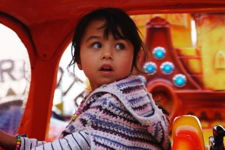 Close-up of cute girl looking away while sitting in ride