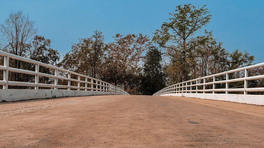 Footpath by footbridge against sky